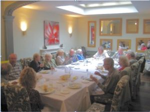 large group having lunch around a long table at St Olaves